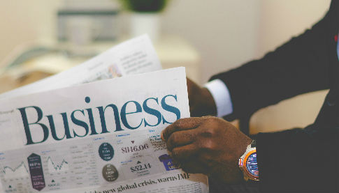 African Canadian man reading business section of the newspaper