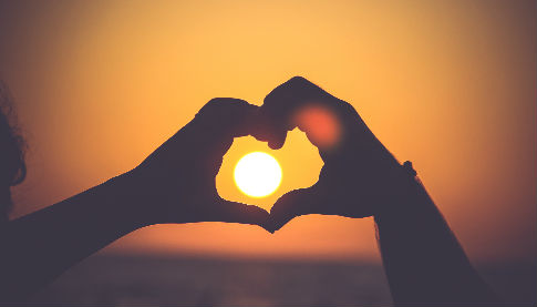 two hands framing the sun in the shape of a heart